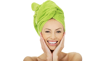 A smiling woman with a towel on her head covering her hair