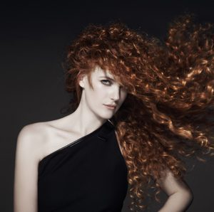 A readhead woman with long curly hair