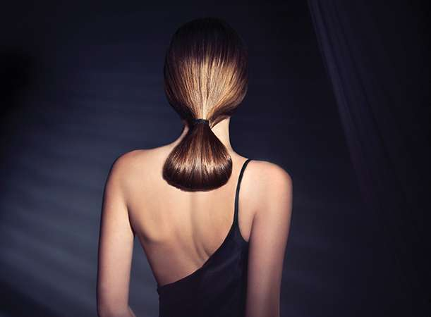 A woman with straightened brown low ponytail