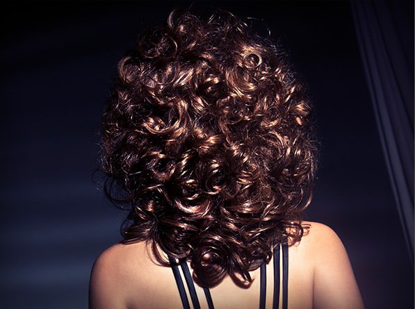 A woman facing back with brown curly hair