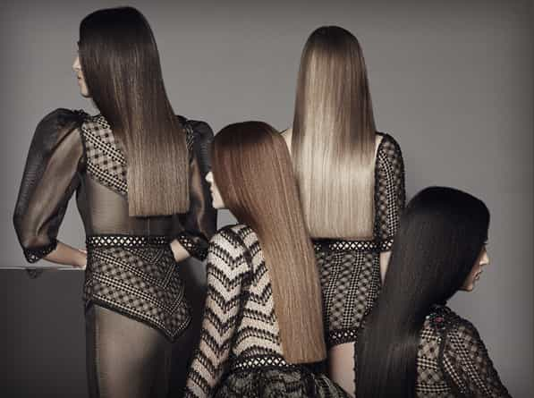 Four women facing back with straight hair, brown, dark brown hair, blonde and black